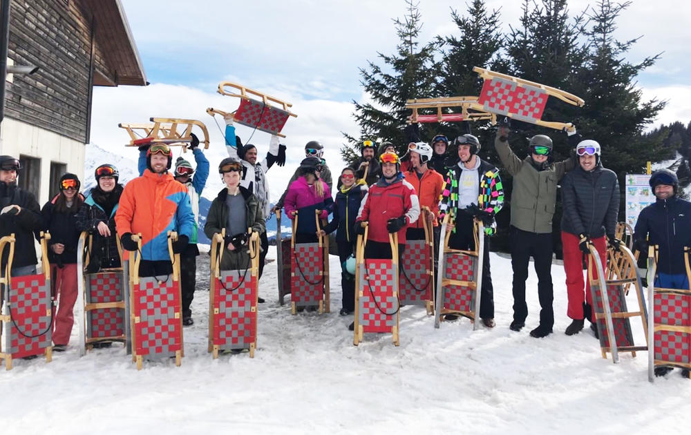 group photo of people with red and grey sledges in the snow