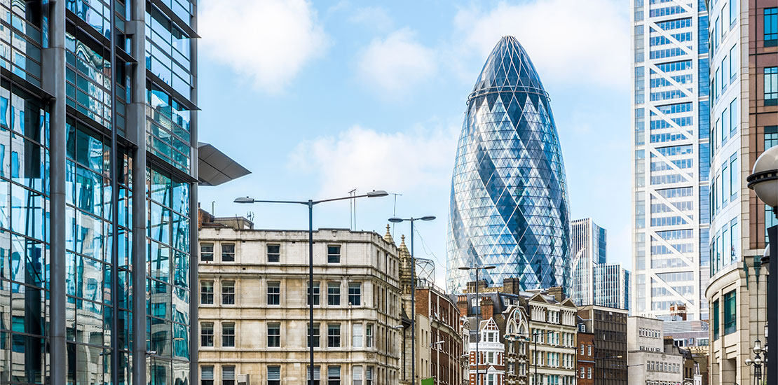 Gherkin buliding in London UK surrounded by other buildings
