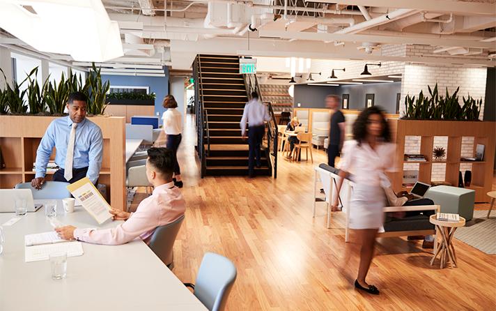 employees working in an open office. Wooden floor. people walking