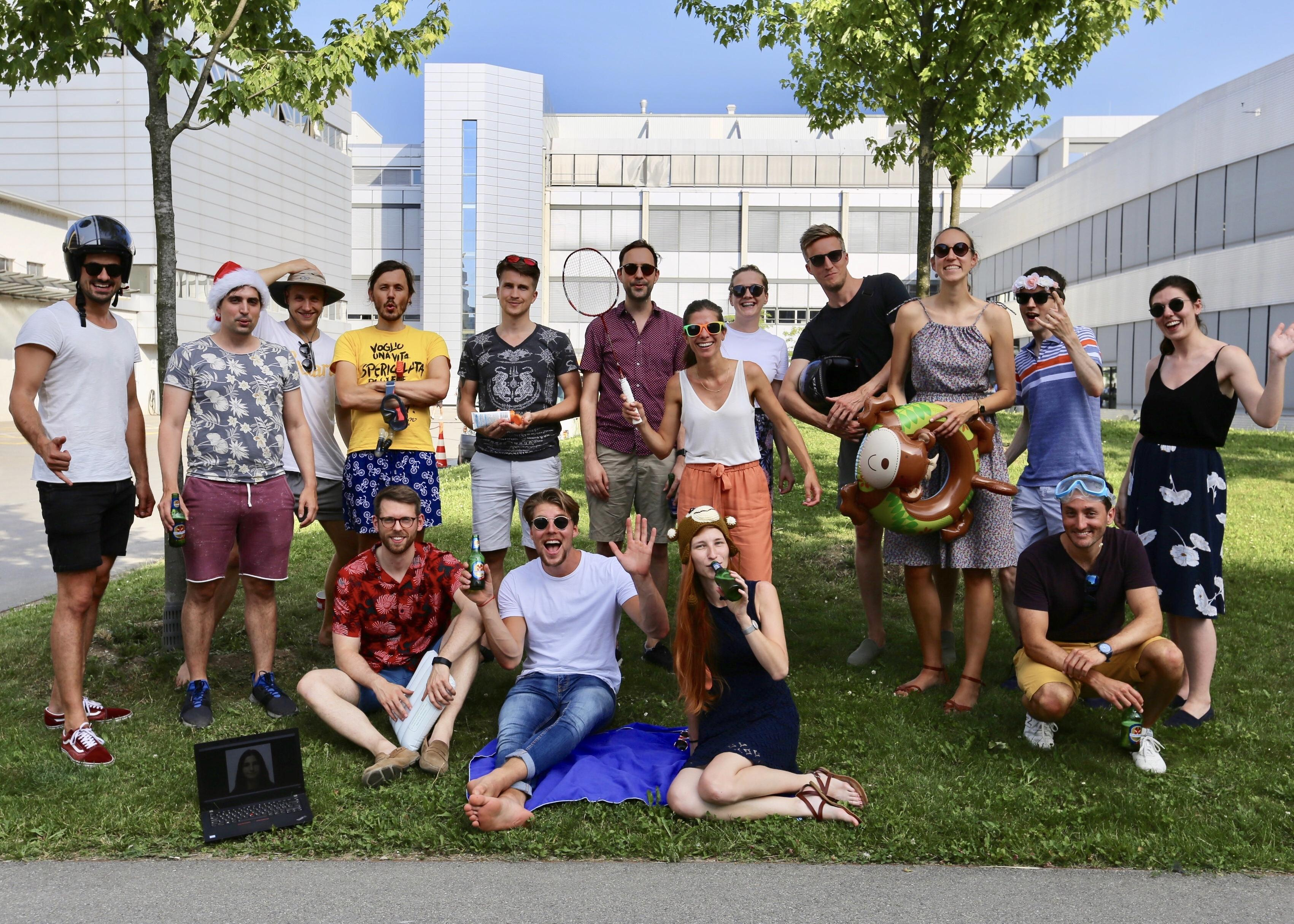 group photo of employees on the grass having fun in summer clothes