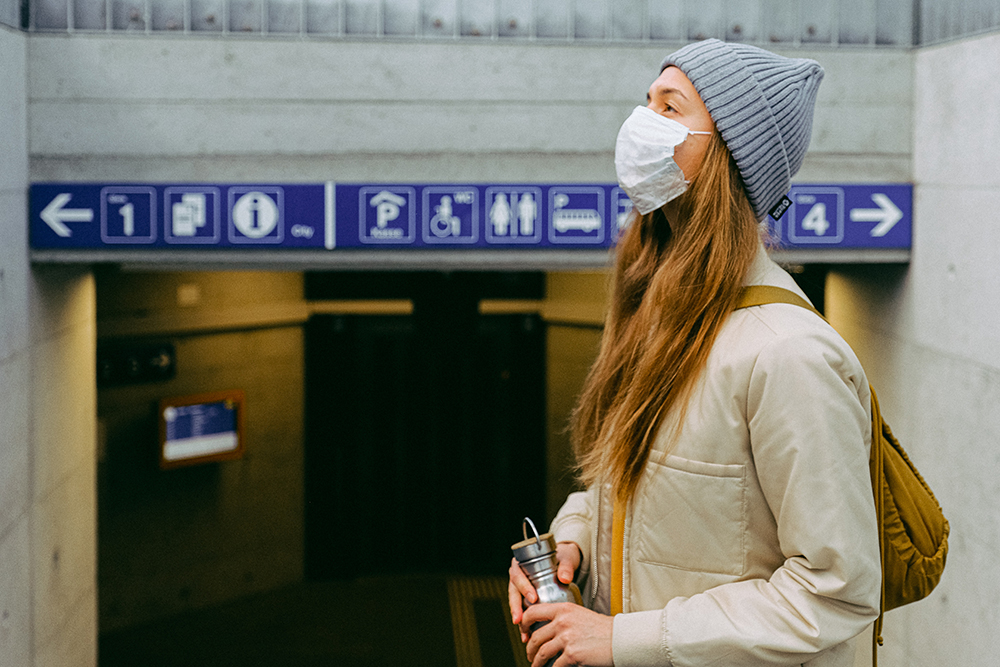 Woman wearing face mask while waiting for public transport