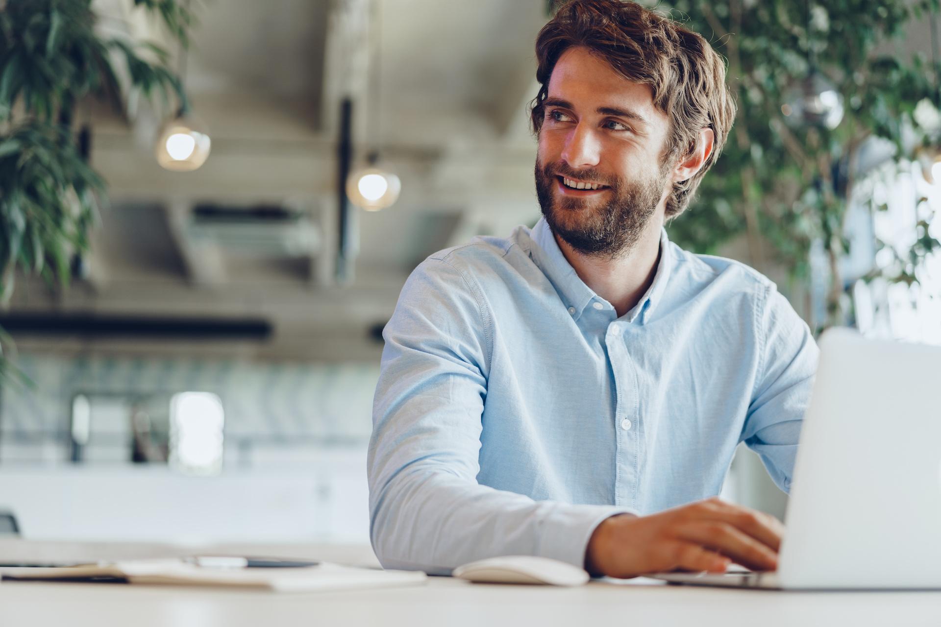 employee blue shirt laptop work smile sit brown hair